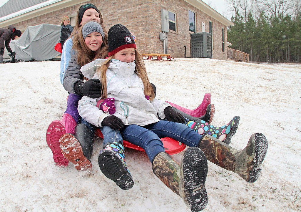 . Julia Jackson, front, Madilyn Bonsall and Madison Jackson sled down a hill on Wednesday, Feb. 12, 2014, in El Dorado, Ark. Most businesses around El Dorado opted to open later in the day after a winter storm dumped a wintery mix on the area. (AP Photo/The El Dorado News-Times, Michael Orrell)