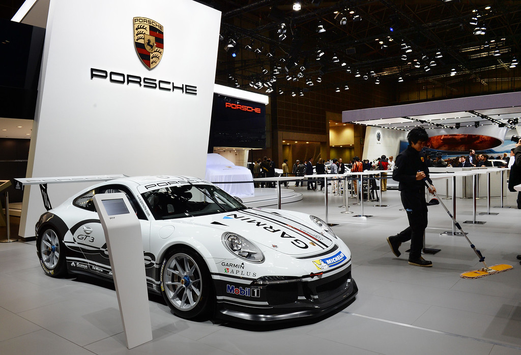 ". A Porsche worker cleans the floor beside a ""911 GT3\"" race car at the company\'s booth at the Tokyo Motor Show in Tokyo on November 20, 2013.      AFP PHOTO / TOSHIFUMI KITAMURA/AFP/Getty Images"
