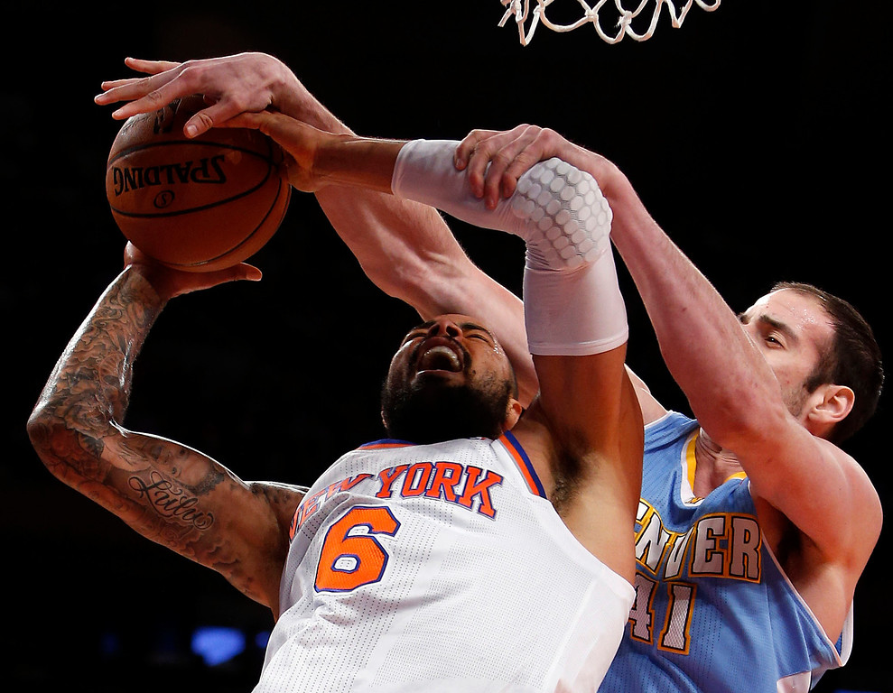 . New York Knicks\' Tyson Chandler (6) is fouled while shooting against Denver Nuggets\' Kosta Koufus (41) during an NBA basketball game, Sunday, Dec. 9, 2012, in New York.  New York beat Denver, 112-106. (AP Photo/Jason DeCrow)