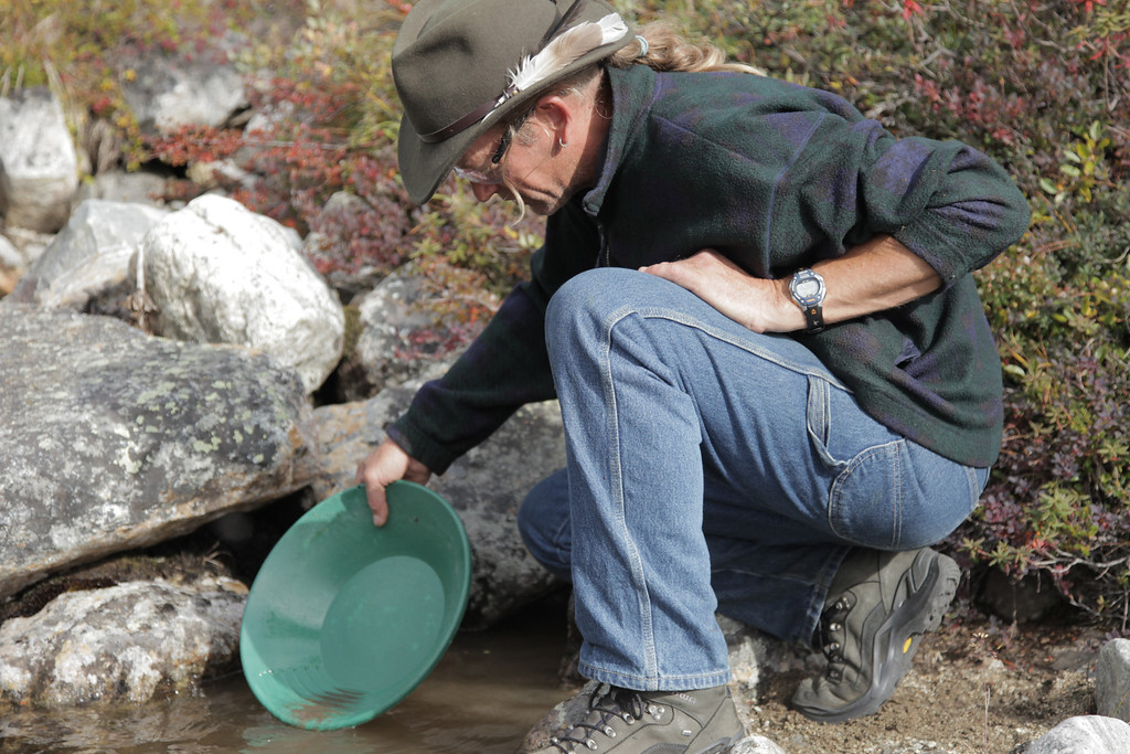 . John Self panning in a creek on Storo Island. Heath Grantham/Discovery Communications
