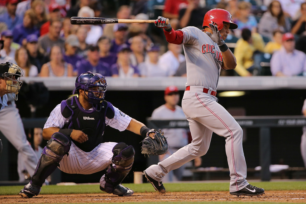 . DENVER, CO - AUGUST 15:  Ramon Santiago #7 of the Cincinnati Reds hits an RBI single off of Nick Masset #37 of the Colorado Rockies to score Jack Hannahan #9 of the Cincinnati Reds and take a 2-1 lead in the fourth inning at Coors Field on August 15, 2014 in Denver, Colorado.  (Photo by Doug Pensinger/Getty Images)