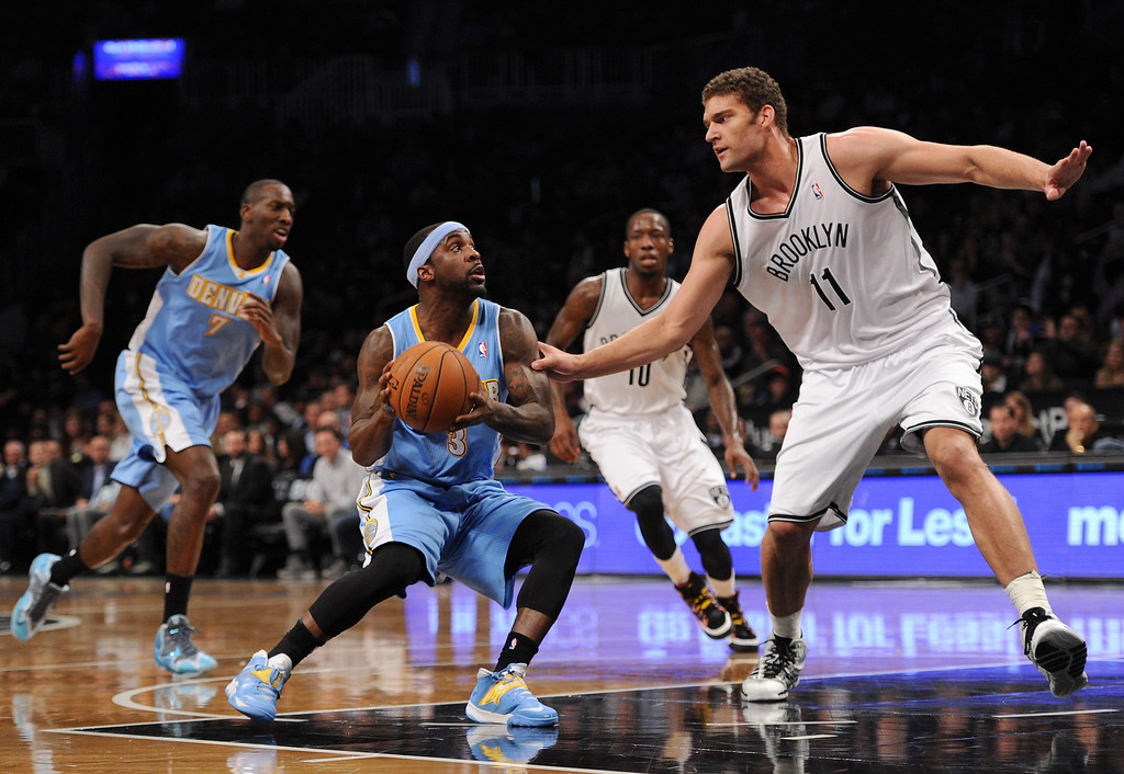. NEW YORK, NY - DECEMBER 03:  Ty Lawson #3 of the Denver Nuggets drives to the basket with pressure from Brook Lopez #11 of the Brooklyn Nets during the first quarter at Barclays Center on December 3, 2013 in the Brooklyn borough of New York City.  (Photo by Maddie Meyer/Getty Images)