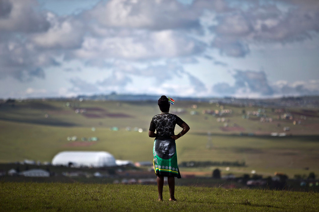 . A mourner wearing a banner as a skirt showing the face of South African President Jacob Zuma observes the scene from a hilltop overlooking the burial site of Nelson Mandela in Qunu, South Africa Sunday, Dec. 15, 2013. (AP Photo/Ben Curtis)