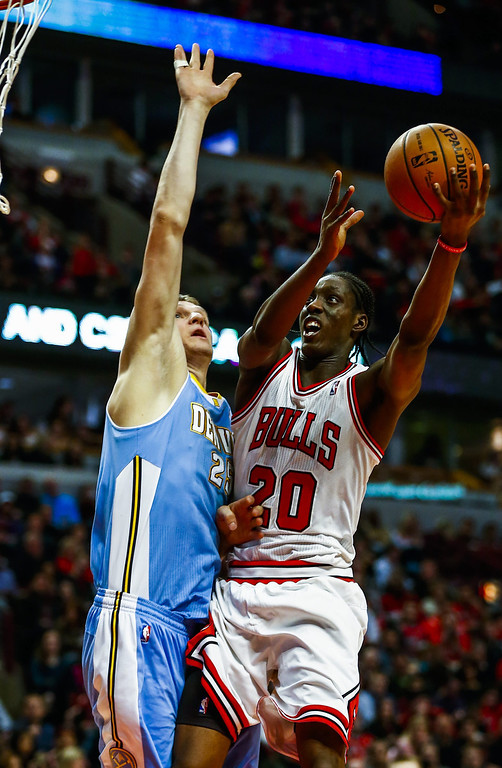 . Chicago Bulls forward Tony Snell (R) shoots over Denver Nuggets center Timofey Mozgov of Russia (L) in the second half of their NBA game at the United Center in Chicago, Illinois, USA, 21 February 2014. The Bulls defeated the Nuggets.  EPA/TANNEN MAURY