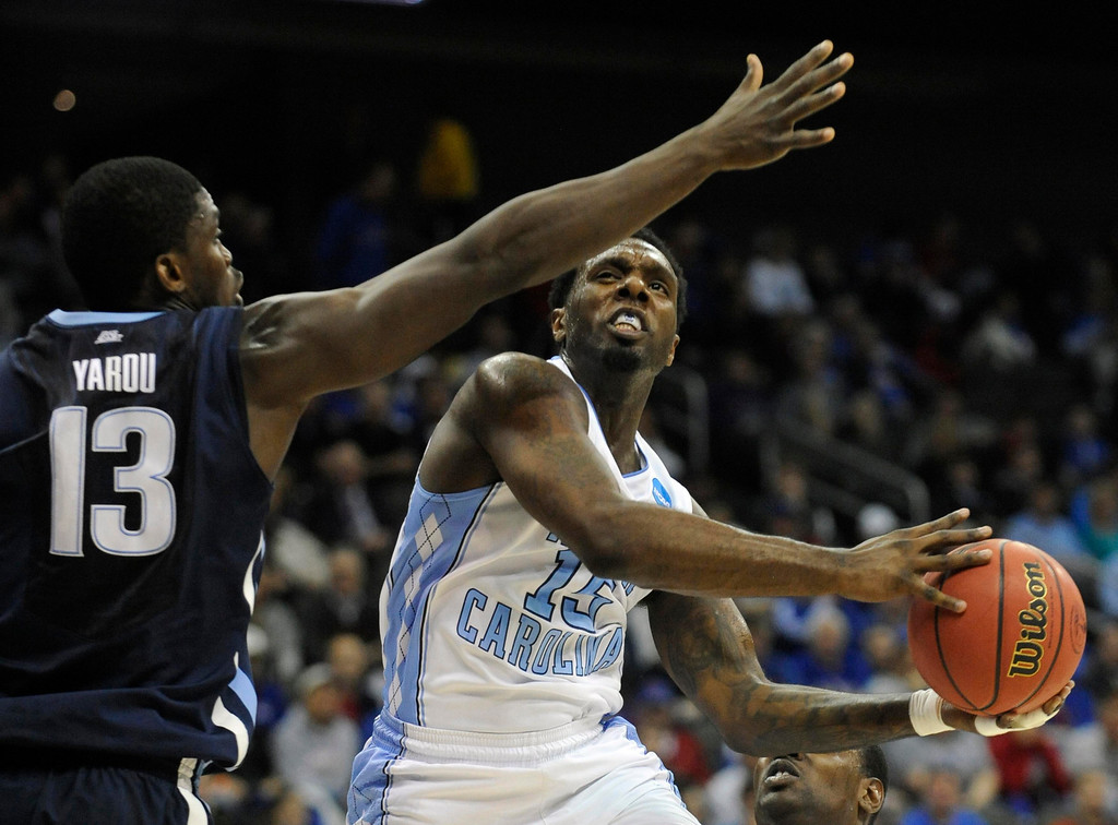 . North Carolina Tar Heels guard P.J. Hairston (R) shoots around Villanova Wildcats forward Mouphtaou Yarou during the first half of the second round of their NCAA men\'s basketball tournament at the Sprint Center in Kansas City, Missouri, March 22, 2013. REUTERS/Dave Kaup