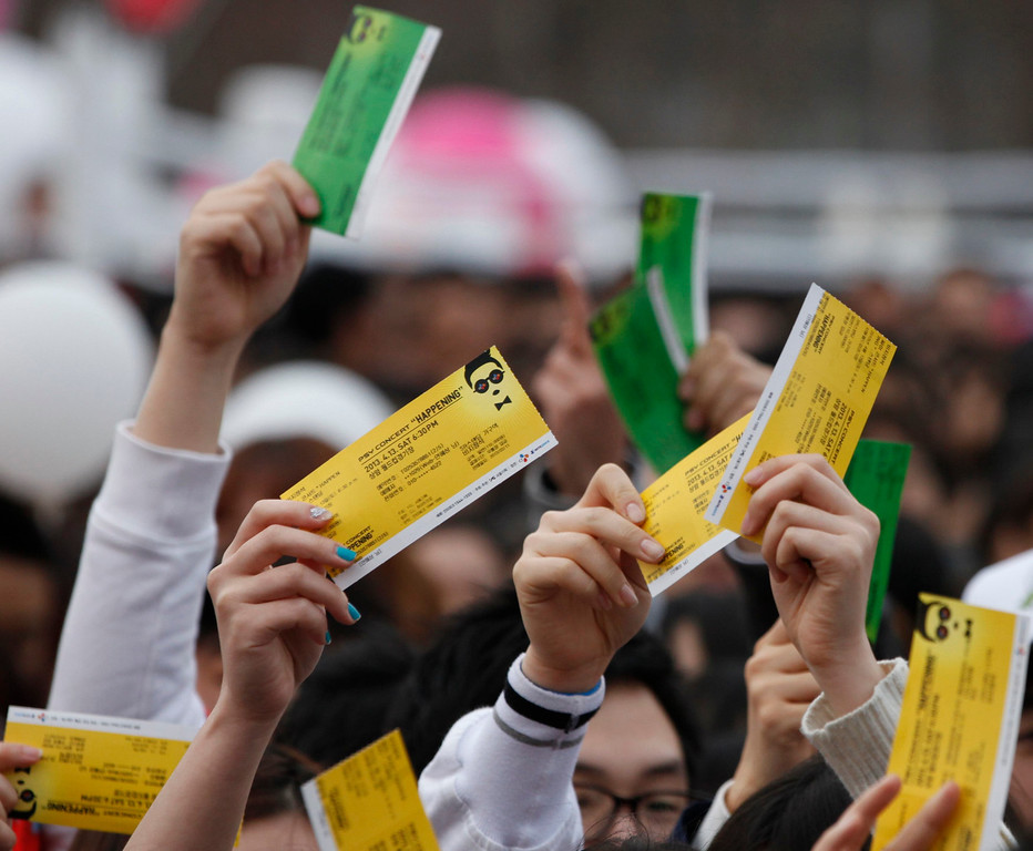 """. Fans of South Korean rapper Psy hold up their concert tickets as they wait in line at the Seoul World Cup stadium, the venue for Psy\'s concert \""""happening\"""" in Seoul April 13, 2013. Psy will perform \""""Gentleman\"""" in public for the first time on Saturday at a concert at Seoul\'s World Cup stadium but he has been coy about what dance to expect this time, except to hint that it is based on traditional Korean moves. Psy released his new single on Thursday hoping to repeat the success of \""""Gangnam Style\"""" that made him the biggest star to emerge from the growing K-pop music scene.   REUTERS/Kim Hong-Ji (SOUTH KOREA - Tags: ENTERTAINMENT)"""