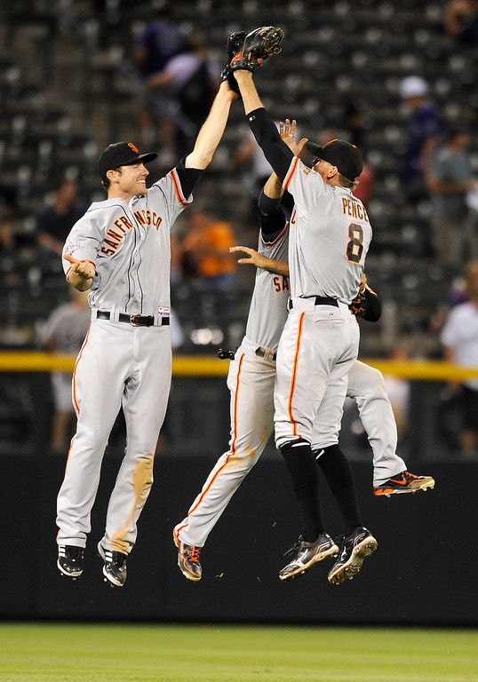 . San Francisco Giants\' Roger Kieschnick, left, Gregor Blanco, center and Hunter Pence celebrate the team\'s 5-3 victory over the Colorado Rockies in a baseball game on Tuesday, Aug. 27, 2013, in Denver. (AP Photo/Jack Dempsey)