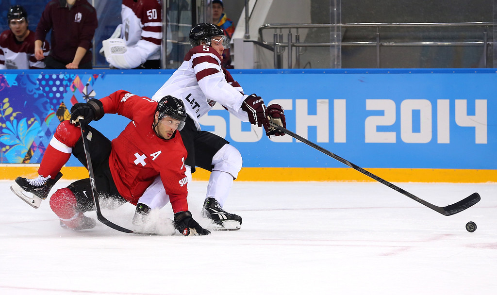 . SOCHI, RUSSIA - FEBRUARY 12: Mark Streit #7 of Switzerland and Janis Sprukts #5 of Latvia fight for a loose puck in the second period during the Men\'s Ice Hockey Preliminary Round Group C game on day five of the Sochi 2014 Winter Olympics at Shayba Arena on February 12, 2014 in Sochi, Russia.  (Photo by Martin Rose/Getty Images)