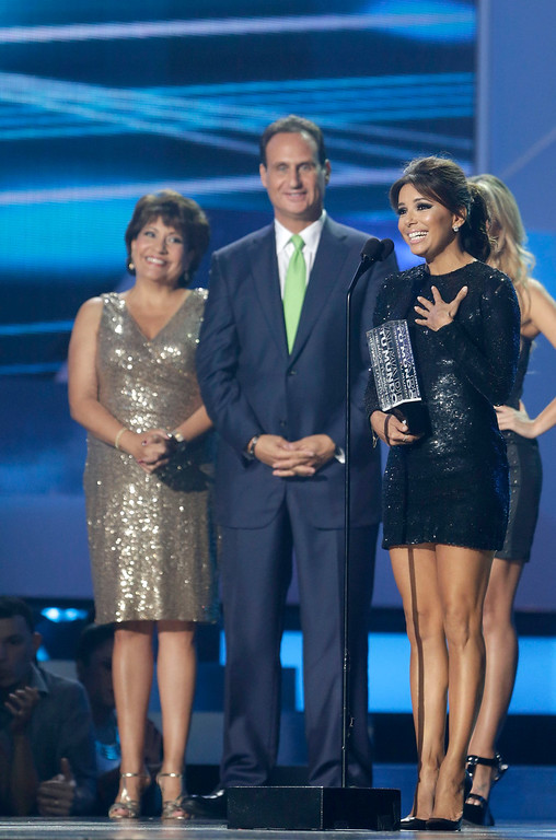 ". Actress Eva Longoria, right, receives the ""Alma de Tu Mundo,\"" (Soul of Your World) award that honors artists who use their fame and talent to help the needy and create awareness of various causes, as presenters, news anchor Jose Diaz-Balart, center, and Janet Murguia, left, president and CEO of the National Council of La Raza, during the Telemundo Spanish language television network\'s \""Premios Tu Mundo,\"" (Your World Awards) show, Thursday, Aug. 15, 2013 in Miami. (AP Photo/Wilfredo Lee)"