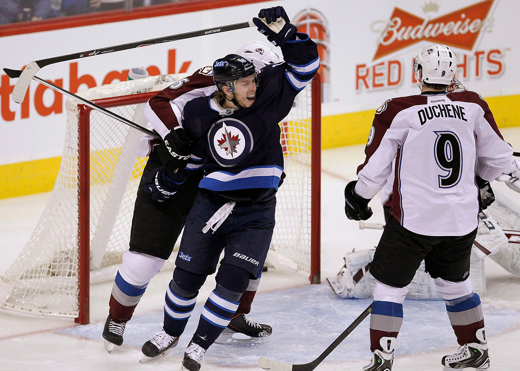 . Winnipeg Jets\' Bryan Little (18) celebrates Blake Wheeler\'s (26) goal against Colorado Avalanche\'s goaltender Semyon Varlamov (1), Erik Johnson (6) and Matt Duchene (9) during first period NHL hockey action in Winnipeg, Manitoba,  on Thursday, Dec. 12, 2013. (AP Photo/The Canadian Press, John Woods)