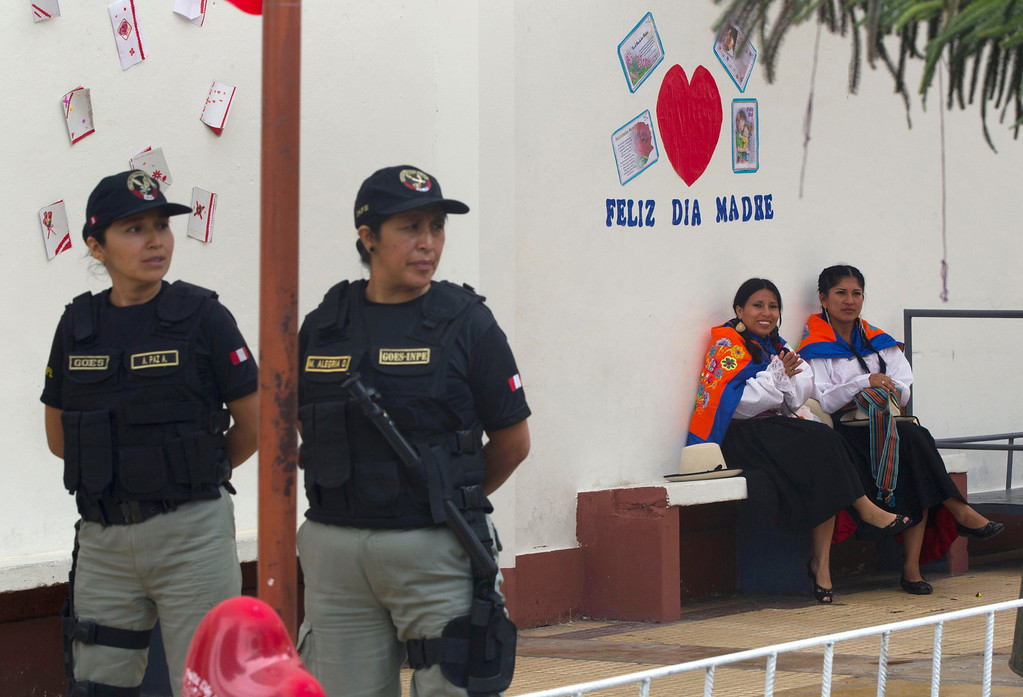 . Police stand guard as two inmates wearing traditional clothes wait their turn to perform at an event celebrating Mother\'s Day at a prison for women in Lima, Peru, Friday, May 10, 2013. Peru celebrates Mother\'s Day every May 10. (AP Photo/Martin Mejia)