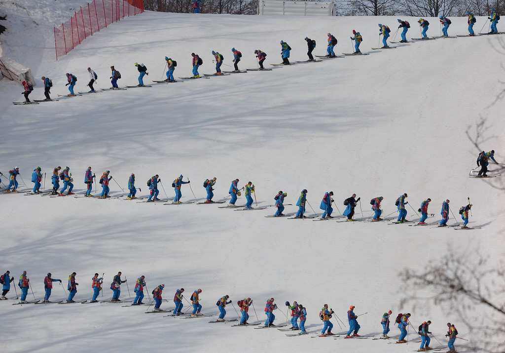 . Volunteers smooth the piste during the Men\'s Alpine Skiing Super-G at the Rosa Khutor Alpine Center during the Sochi Winter Olympics on February 16, 2014. PETER PARKS/AFP/Getty Images