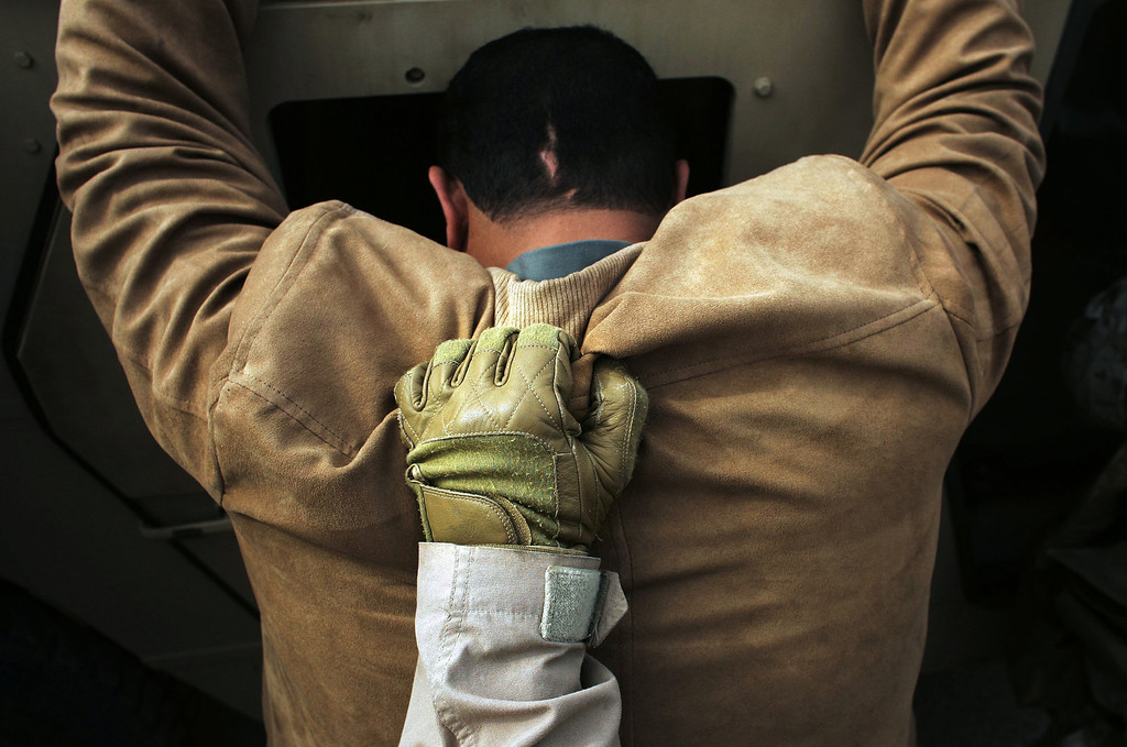 . An Iraqi man is held against a Humvee by a US Marine after being searched during snap vehicle checks on February 8, 2006 in Ramadi, Iraq.  Marines of the 3rd Battalion, 7th Regiment frequently took to Ramadi\'s tense streets in Humvee convoys, randomly stopping vehicles to search for weapons and insurgents.  Sniper attacks were common, so the Marines usually set off smoke bombs to screen them from attackers.  (Photo by Chris Hondros/Getty Images)