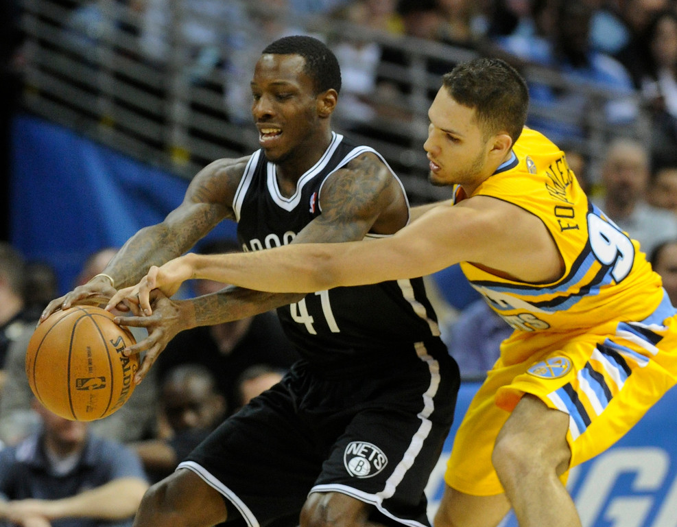 . DENVER, CO. - MARCH 29: Evan Fournier (94) of the Denver Nuggets reached for the ball controlled by Tyshawn Taylor (41) of the Brooklyn Nets in the first half. The Denver Nuggets hosted the Brooklyn Nets Friday night, March 29, 2013 at the Pepsi Center in Denver.  (Photo By Karl Gehring/The Denver Post)