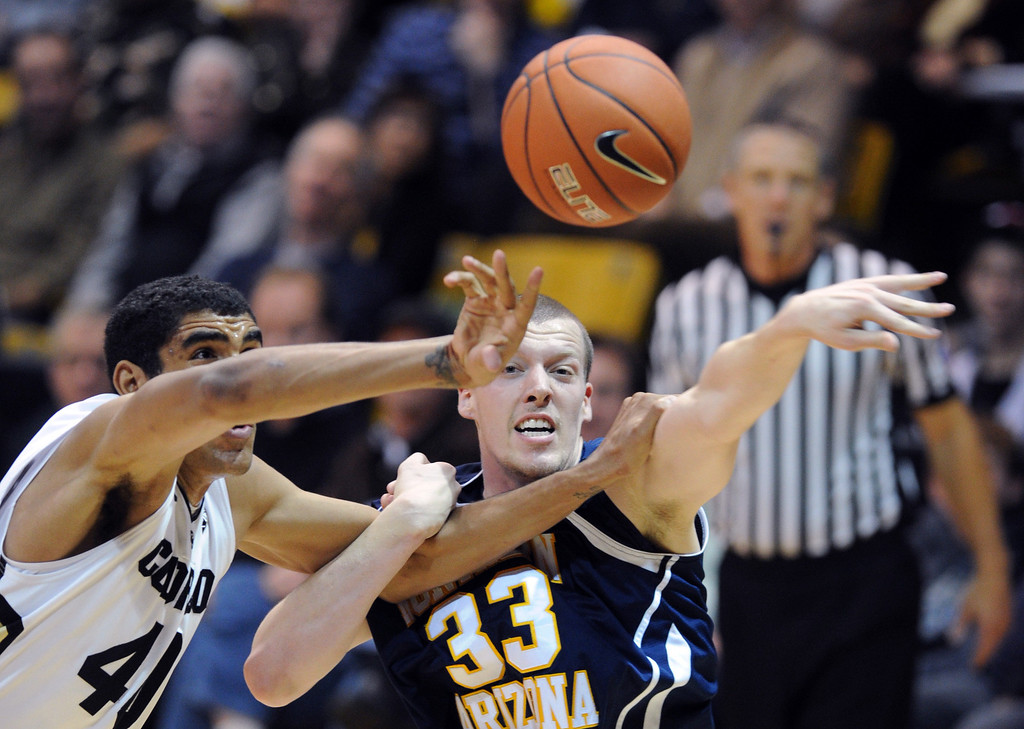 . Josh Scott, left, of Colorado, knocks the ball from Max Jacobsen of Northern Arizona during the first of the December 21, 2012 game in Boulder. Cliff Grassmick / December 21, 2012