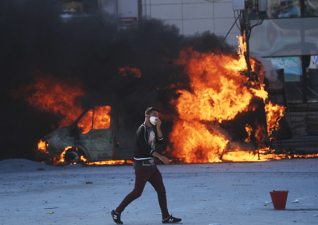 . A man walks in front of a burning car during clashes with police on Taksim square in Istanbul, on June 11, 2013. AFP PHOTO/BULENT KILIC/AFP/Getty Images