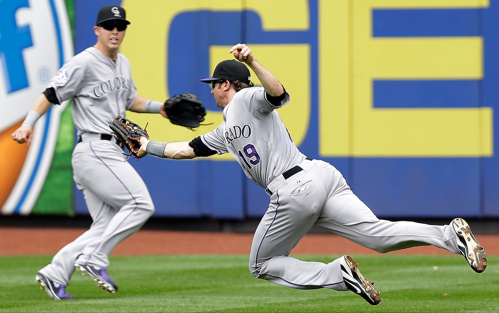 . Colorado Rockies center fielder Corey Dickerson, left, watches as right fielder Charlie Blackmon (19) dives and makes the catch on a fly ball by New York Mets\' Juan Lagares in the fifth inning of a baseball game in New York, Thursday, Aug. 8, 2013. The Mets won 2-1.  (AP Photo/Kathy Willens)