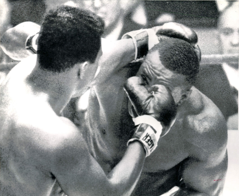 . Cassius Clay, left, bangs a right to the face of Sonny Liston during heavyweight championship fight in Miami Beach, Fla. tonight.  Liston, suffering a cut left eye and a strained shoulder, lost his crown on a seventh round. 1964   AP Wirephoto