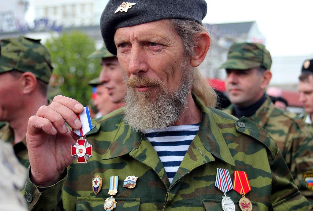 ". A member of pro-Russian self defense forces shows his medal ""For the Defence of Crimea\"" recently established by the local authorities in Simferopol on April 13, 2014, during in a ceremony to celebrate the 70th anniversary of the peninsula\'s capital Simferopol liberation from Nazi Germany troops during the World War II. Crimea\'s largely Russian-speaking residents voted in March to become part of Russia, in a hastily organised referendum held as Russian troops patrolled the region.  AFP PHOTO/ YURIY LASHOV"