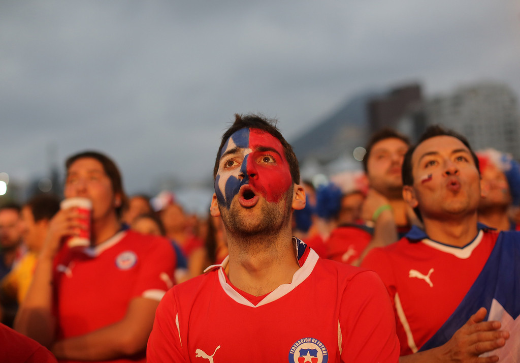 . Soccer fans watch a live broadcast of the group B World Cup match between Chile and Spain, inside the FIFA Fan Fest area on Copacabana beach, in Rio de Janeiro, Brazil, Wednesday, June 18, 2014. Chile defeated Spain, the defending champs, 2-0. (AP Photo/Leo Correa)