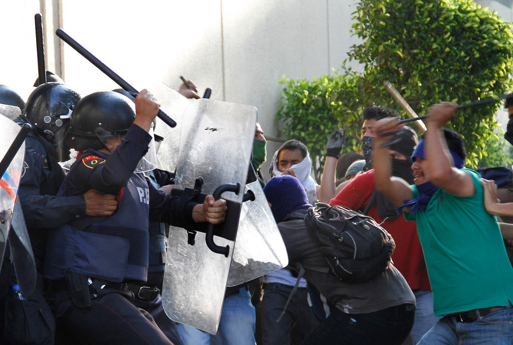 . Protesters and police clash during a march marking the anniversary of the Tlatelolco massacre in Mexico City, Wednesday, Oct. 2, 2013.  Mexico commemorated the 45th anniversary of the massacre of students holding an anti-government protest, killed by men with guns and soldiers in 1968 days before the Summer Olympics celebrations in Mexico City.  (AP Photo/Marco Ugarte)
