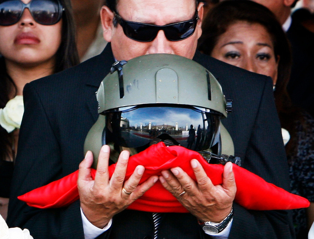 . The father of Captain Nancy Flores kisses her pilot helmet during her funeral in Lima April 14, 2012. Flores was killed and three other police officers wounded in an armed encounter with Shining Path rebels on April 12, during a rescue mission to free hostages held by the rebels in a remote jungle region around the Ene and Apurimac valleys (VRAE) of southeastern Peru.REUTERS/Vera Lentz