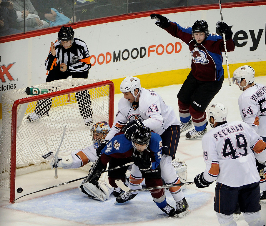 . Colorado Avalanche right wing David Jones (54) knocks in the winning goal in overtime as he gets hit from behind by Edmonton Oilers defenseman Jason Strudwick (43) April 10, 2011 at Pepsi Center. The Avalanche defeated the Oilers 4-3.  John Leyba, The Denver Post