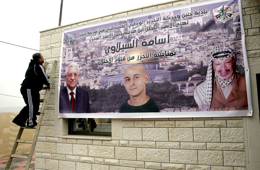 """. A Palestinian relative of Osama Al-Selawai hangs a poster with his picture in the middle, with pictures of Palestinian President, Mahmoud Abbas, left, and former President Yasser Arafat, right, at Al-Selawai\'s home in the West Bank city of Jenin, Monday, Dec. 30, 2013. Al-Selawai is one of 26 long-serving Palestinian prisoners who were convicted in connection to the killing of Israelis, that Israel announced  it will release this week under a U.S.-brokered formula to resume Mideast peace talks. Arabic reads, \""""Jenin municipality and the Palestinian National Liberation Movement - Fatah (Jenin city), congratulates Jenin son, the free prisoner, Osama Al-Selawai, for his freedom from the shackles of occupation.\"""" (AP Photo/Mohammed Ballas)"""