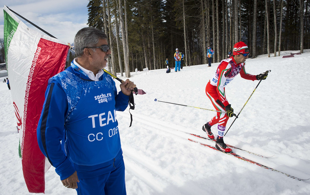 . An Iranian team member watches as Iran\'s Seyed Sattar Seyd competes in the Men\'s Cross-Country Skiing 15km Classic at the Laura Cross-Country Ski and Biathlon Center during the Sochi Winter Olympics on February 14, 2014 in Rosa Khutor near Sochi. AFP PHOTO / ODD ANDERSEN/AFP/Getty Images