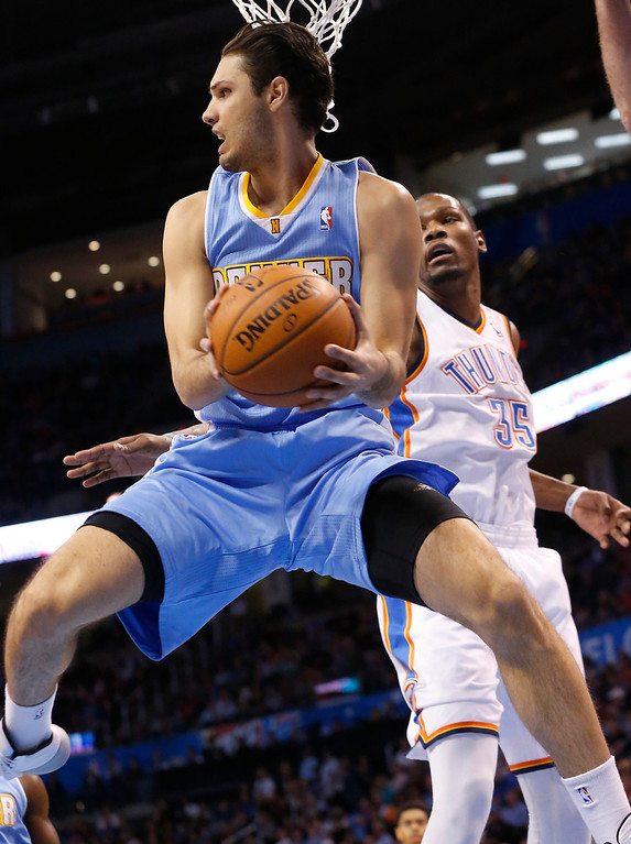 . Denver Nuggets guard Evan Fournier drives under the basket past Oklahoma City Thunder forward Kevin Durant (35) in the first quarter of an NBA basketball game in Oklahoma City, Monday, March 24, 2014. (AP Photo/Sue Ogrocki)