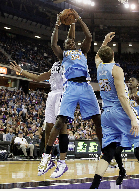 . Denver Nuggets forward Kenneth Faried, center, grabs a rebound away from Sacramento Kings forward Carl Landry, as Nuggets center Timofey Mozgov, right, of Russia, looks on during the fourth quarter of an NBA basketball game in Sacramento, Calif., Sunday, Jan. 26, 2014. The Nuggets won 125-117.(AP Photo/Rich Pedroncelli)