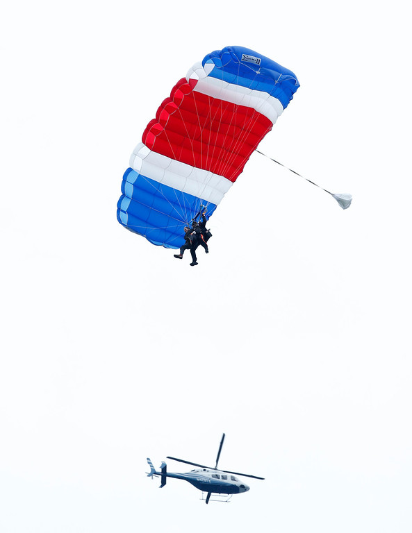 . Former President George H.W. Bush, strapped to Sgt. 1st Class Mike Elliott, a retired member of the Army\'s Golden Knights parachute team, float to the ground during a tandem parachute jump near Bush\'s summer home in Kennebunkport, Maine, Thursday, June 12, 2014. Bush made the jump, his eighth, in celebration of his 90th birthday. (AP Photo/Robert F. Bukaty)