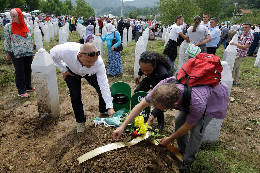 . Dutch soldiers, ex-members of the  UN mission to guard the enclave of Srebrenica, Adje Anakotta, center, Dion Vandenberg, right, and Dave Maat, left, at the graveside of baby Muhic during a mass funeral for Srebrenica victims at the memorial center in Potocari, near Srebrenica, 160 kms east of Sarajevo, Bosnia, Thursday, July 11, 2013. Mother, Hava Muhic, believes she should be baking a cake, with her husband calling friends and family for a party, instead, Muhic stood Thursday above the smallest pit in the cemetery, near her husband\'s grave. It was dug for her baby girl ,who was born and died here 18 years ago on the day of the worst massacre Europe has seen since World War II. Muhic\'s baby is among 409 newly identified victims of the Srebrenica massacre buried Thursday in an annual mass funeral at the Potocari Memorial Center on the July 11 anniversary. This year\'s commemorations bring the total of identified victims to 6,066. Another 2,306 remain missing.  (AP Photo/Amel Emric)