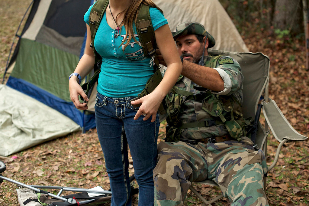 ". A member of the North Florida Survival Group helps his daughter put on a tactical harness as they gear up to perform enemy contact drills in a wooded area during a field training exercise in Old Town, Florida, December 8, 2012. The group trains children and adults alike to handle weapons and survive in the wild. The group passionately supports the right of U.S. citizens to bear arms and its website states that it aims to teach ""patriots to survive in order to protect and defend our Constitution against all enemy threats\"". Picture taken December 8, 2013.   REUTERS/Brian Blanco"