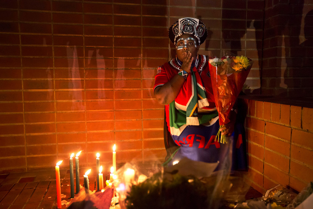 . Soweto resident Joy Chauke pauses as she lays flowers outside the old house of Nelson Mandela in Soweto, Johannesburg, South Africa Friday, Dec. 6, 2013. Flags were lowered to half-staff and people in black townships, in upscale mostly white suburbs and in South Africa\'s vast rural grasslands commemorated Nelson Mandela with song, tears and prayers on Friday while pledging to adhere to the values of unity and democracy that he embodied. (AP Photo/Ben Curtis)