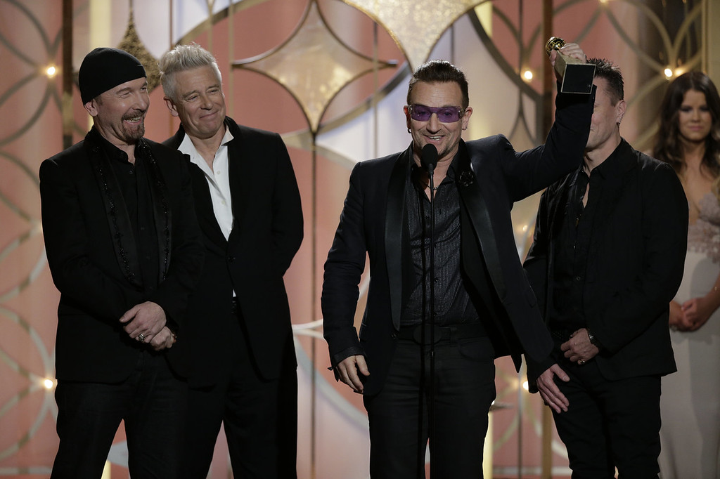 ". In this handout photo provided by NBCUniversal, (L-R) The Edge, Adam Clayton, Bono and Larry Mullen, Jr. of U2, accept the award for Best Original Song - Motion Picture for ""Ordinary Love\"" from \""Mandela: Long Walk to Freedom\"" during the 71st Annual Golden Globe Award at The Beverly Hilton Hotel on January 12, 2014 in Beverly Hills, California.  (Photo by Paul Drinkwater/NBCUniversal via Getty Images)"