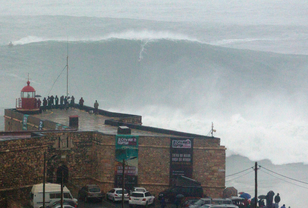 . Brazilian surfer Carlos Burle rides a big wave at the Praia do Norte, north beach, outside the fishing village of Nazare in Portugal\'s Atlantic coast Monday, Oct. 28 2013. Surf media suggest it could be the biggest wave ever surfed. According to Guinness World Records, American Garret McNamara holds the record with a 78 feet wave surfed at the very same spot in Nazare in Nov. 1 2011. (AP Photo/Miguel Barreira)