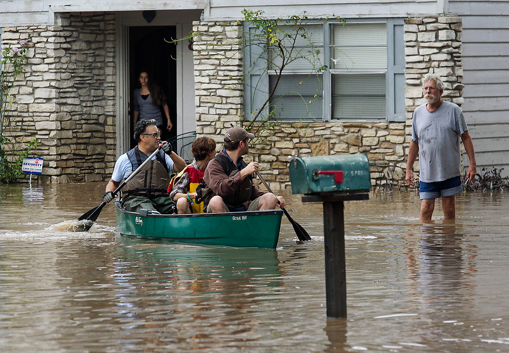 . People paddle through flooded streets in Austin, Texas, on Thursday, Oct. 31, 2013. Heavy overnight rains brought flooding to the area. (AP Photo/Austin American-Statesman, Ralph Barrera)