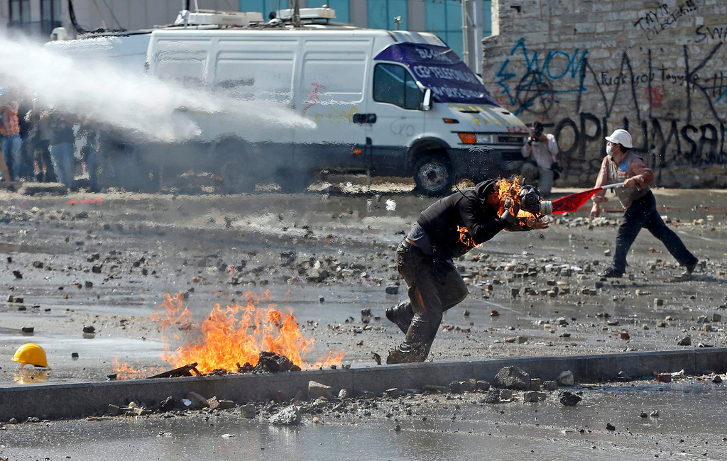 . A protester catches fire as the throws a petrol bomb at riot police during a protest at Taksim Square in Istanbul June 11, 2013.  REUTERS/Murad Sezer