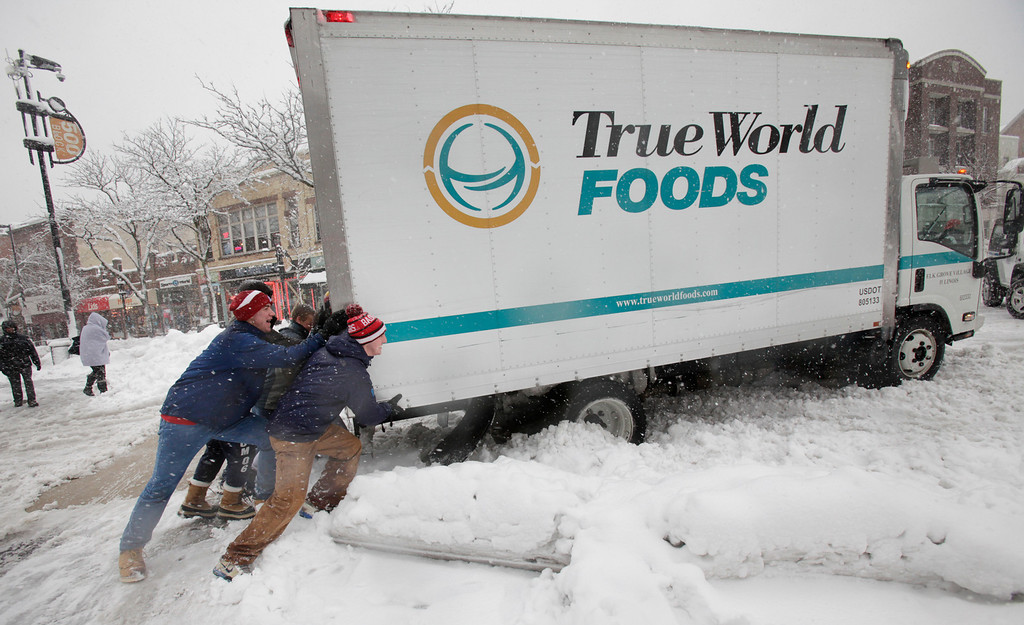. A group of University of Wisconsin-Madison students assist a food delivery truck driver in freeing his truck after making a stop at Wasabi Japanese Restaurant on State Street in Madison, Wis., Thursday afternoon, Dec. 20, 2012. They were not successful. (AP Photo/Wisconsin State Journal, M.P. King)