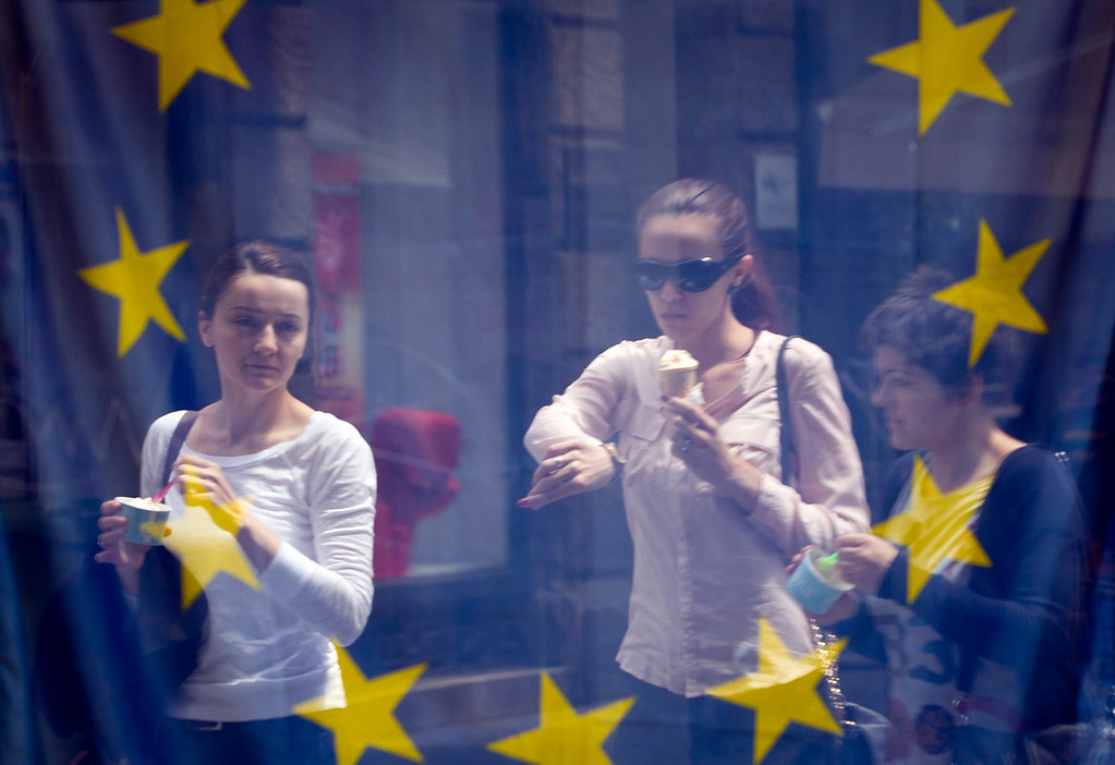 . A street scene is reflected in the window of a library with an EU flag on display  in downtown  Zagreb, Croatia, Sunday, June 30, 2013. Croatia is to join the European Union on July 1, 2013. (AP Photo/Darko Bandic)