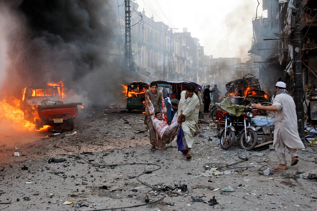 . Pakistani men carry an injured man away from the site moments after a car bomb attack in Peshawar, Pakistan, Sunday, Sept. 29, 2013. (AP Photo/Mohammad Sajjad)