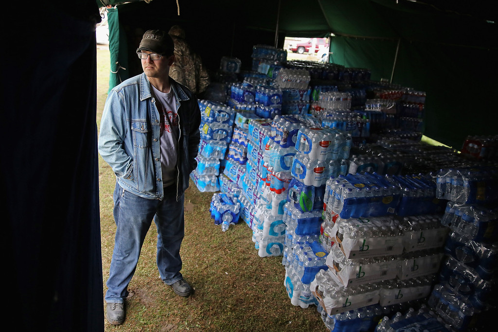. WEST, TX - APRIL 18:  West native and Texas A&M theater teacher Justin A. Miller helps distribute donated bottles of water outside the West Community Center the day after the West Fertilizer Company explosion April 18, 2013 in West, Texas. The fertilizer company caught fire and exploded, killing more than five people, injuring more than 160 people and leaving damaged buildings for blocks in every direction.  (Photo by Chip Somodevilla/Getty Images)