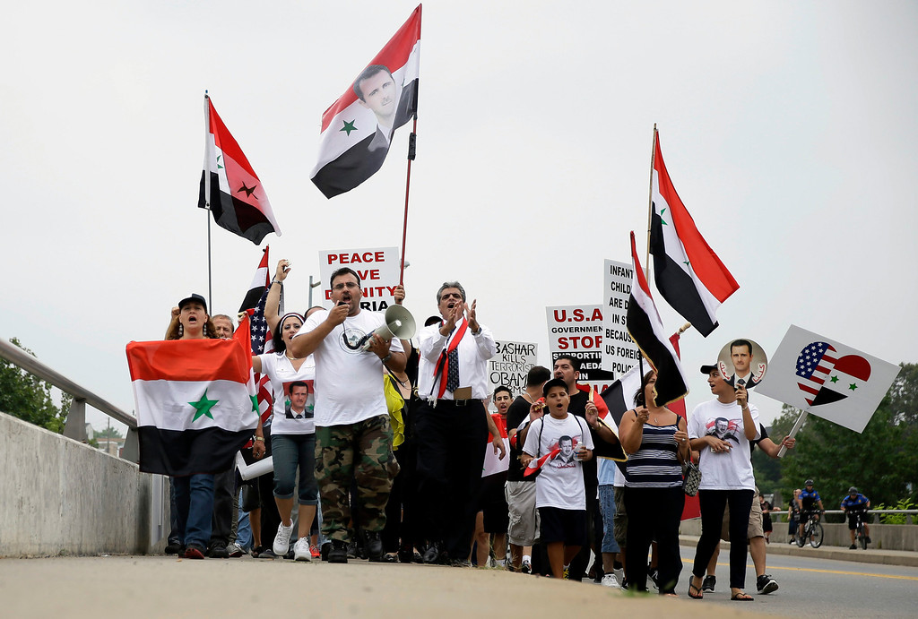. Members of the local Syrian community march in protest against the United States\' involvement in Syria, Friday, Aug. 30, 2013, in Allentown, Pa. President Barack Obama says he hasn\'t made a final decision about a military strike against Syria_but is considering a limited and narrow action in response to a chemical weapons attack that he says Syria\'s government carried out last week. (AP Photo/Matt Slocum)
