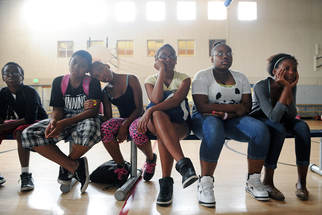 """. DENVER, CO - JULY 1:  From left to right; Dashawn Tolbert, 13, Jaisen White, 13, Kiyara Copney, 14, Tyra Goodluck, Davion Applewhite, 16 and Kimyara Gay-Blake, 14, watch a documentary on farming practices in the United States during a summer camp at St. Charles Recreation Center at 3777 Lafayette Street in Denver, CO. on July 1, 2013.  DJ Cavem Moetavation and his wife Neambe Leadon Vita, not shown, hold the camp to introduce kids to healthy eating habits, teach them about organic farming and changing the way they think about food. They also make organic juice during the day using produce from the couple\'s garden which includes cucumbers, strawberries, watermelon, kale, lime and coconut water.   As part of our \""""Summer of Love\"""" series for the Style section we profile the relationship of DJ Cavem Moetavation (a.k.a. Ietef Vita) and his wife Neambe Vita.  They are proud and longtime Five Points residents. They\'re artists, community activists, musicians, teachers and more.  They espouse the idea of being vegan or vegetarian and promote eating healthfully and organically.  (Photo by Helen H. Richardson/The Denver Post)"""