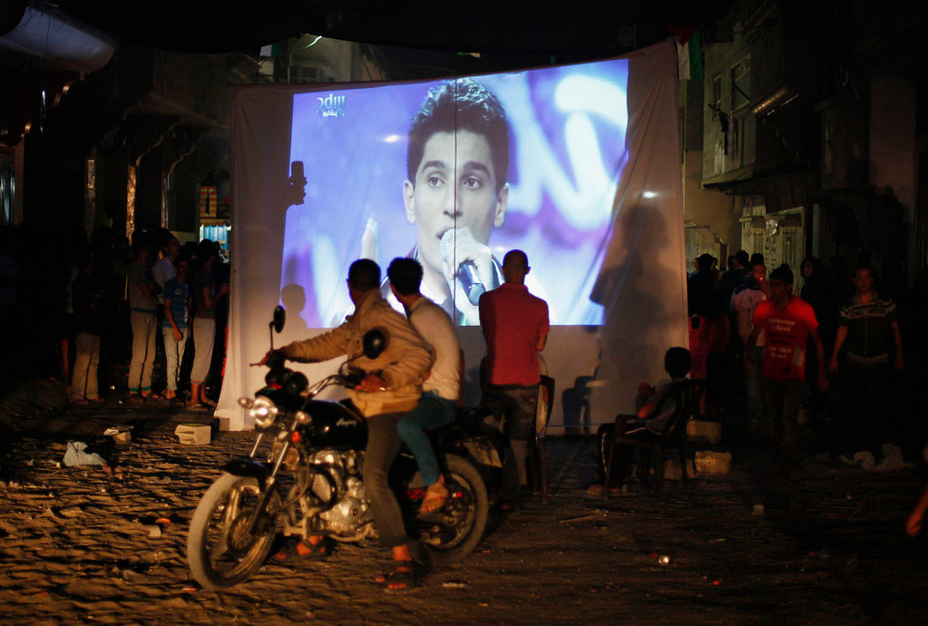 ". People watch Palestinian singer Mohammed Assaf as he sings in Beirut during the ""Arab Idol\"" program, in Khan Younis in the southern Gaza Strip June 22, 2013. The 22-year-old singer Mohammed Assaf, from the Gaza Strip, was named the winner of \""Arab Idol\"" in a TV talent contest in Beirut.  REUTERS/Ibraheem Abu Mustafa"