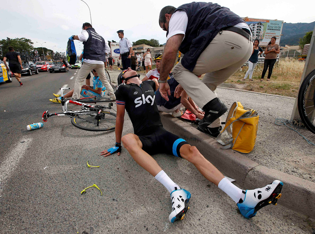. Team Sky rider Geraint Thomas of Britain sits on the road after he fell at 5 kilometers before the finish  in the 213 km first stage of the centenary Tour de France cycling race from Porto-Vecchio to Bastia, on the French Mediterranean island of Corsica June 29, 2013.    REUTERS/Eric Gaillard