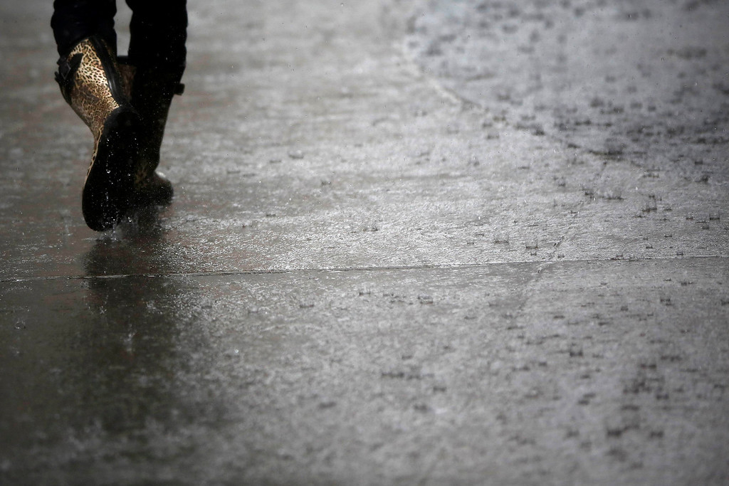 . A woman walks through Times Square during a rainstorm in New York June 13, 2013. A severe storm system sweeping the U.S. East Coast on Thursday delayed flights and threatened to snarl work commutes a day after causing several tornadoes, damaging hail and high winds across the upper Midwest.  REUTERS/Shannon Stapleton