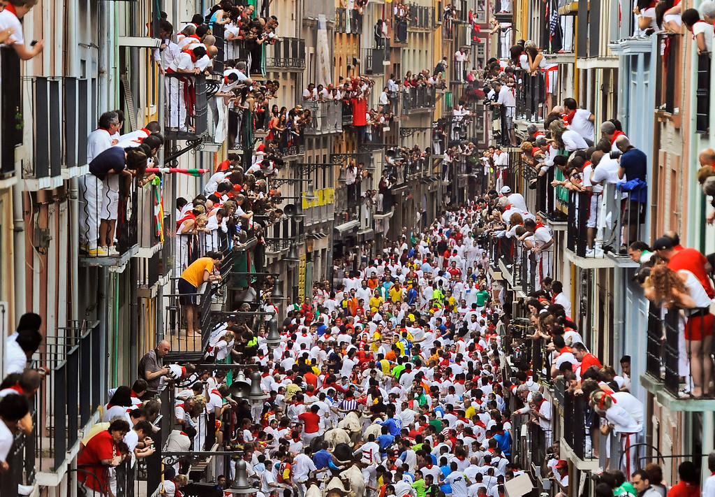""". Runners make their way through the street with \""""El Pilar\"""" fighting bulls watched by people from their balconies during the running of the bulls at the San Fermin festival, in Pamplona, Spain, Friday, July 12, 2013. Revelers from around the world arrive to Pamplona every year to take part in some of the eight days of the running of the bulls glorified by Ernest Hemingway\'s 1926 novel \""""The Sun Also Rises.\"""" (AP Photo/Alvaro Barrientos)"""