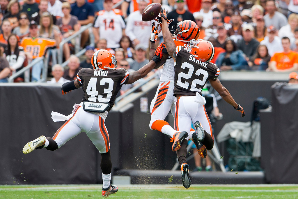 . CLEVELAND, OH - SEPTEMBER 29: Wide receiver Mohamed Sanu #12 of the Cincinnati Bengals ties to make the catch under pressure from strong safety T.J. Ward #43 and cornerback Buster Skrine #22 of the Cleveland Browns during the first half at FirstEnergy Stadium on September 29, 2013 in Cleveland, Ohio. (Photo by Jason Miller/Getty Images)